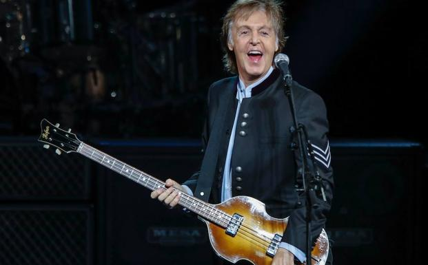 McCartney toca la guitarra en un concierto.