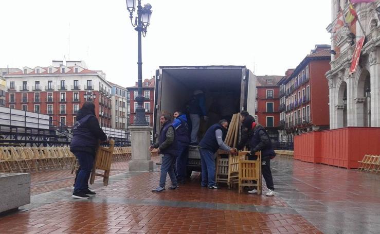 Operarios retiran las sillas de la Plaza Mayor de Valladolid colocadas para la Procesión General suspendida por la lluvia