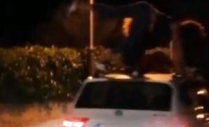 Graban a dos jóvenes bailando sobre un coche en marcha