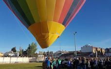 La talla de San Isidro sufre un percance al aterrizar el globo, que se desvió por el fuerte viento