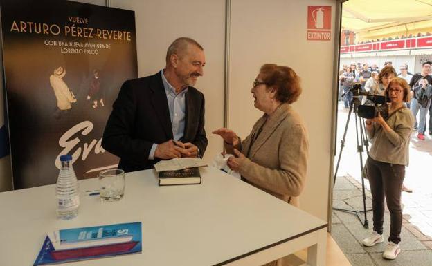 Arturo Pérez-Reverte charla con una lectora en la caseta de firmas de la Plaza Mayor. /G. Villamil