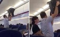 Intenta meter una maleta en el compartimento del avión pero no sale bien