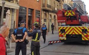 La moldura de un edificio de la Calle Mayor de Palencia cae sobre la terraza de un bar