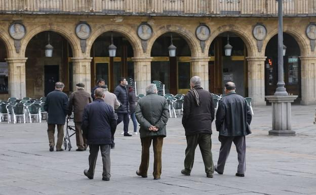 Un grupo de mayores pasea por la Plaza Mayor.