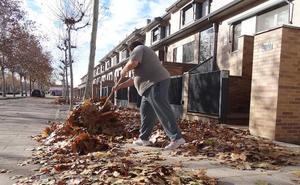 Los vecinos de la Cañada Real de Valladolid tiran de escoba para limpiar las aceras de hojas
