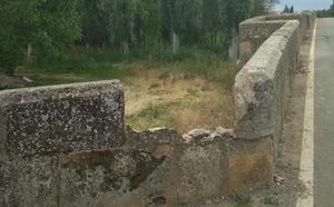 Un tractor rompe a su paso parte del puente romano de Cea