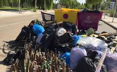 Medio centenar de jóvenes sacan quince contenedores de basura de la ribera del Pisuerga en Valladolid