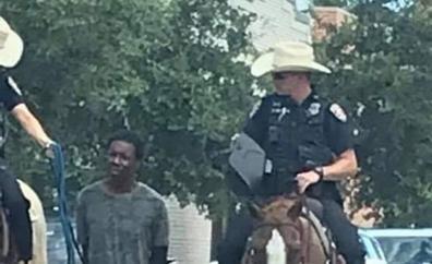 Dos policías a caballo llevan a un hombre negro esposado y atado con una cuerda en Estados Unidos