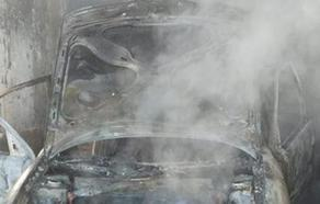Los bomberos sofocan un incendio de un coche en una nave agrícola de Cabezón