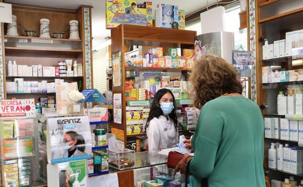 La farmaceutica María Ruiz atiende a una usuaria./MANUEL BRÁGIMO