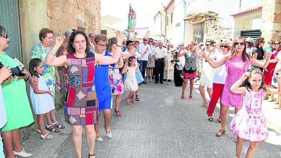 Niñas y mayores danzan en honor a la patrona. /